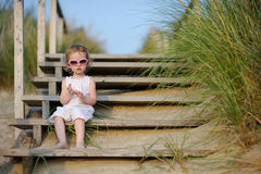 Adorable toddler girl sitting on the stairs. By the sea Royalty Free Stock Image