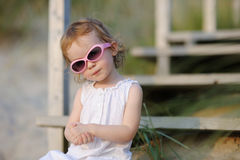 Adorable toddler girl sitting on the stairs Stock Image
