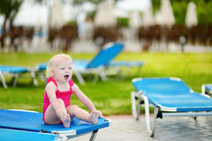 Adorable toddler girl sitting on a sunbed Stock Image