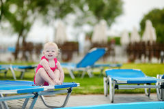 Adorable toddler girl sitting on a sunbed Royalty Free Stock Photo