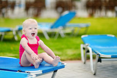 Adorable toddler girl sitting on a sunbed Stock Photo