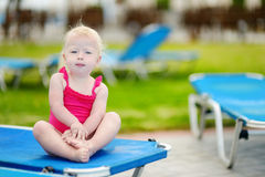 Adorable toddler girl sitting on a sunbed Royalty Free Stock Photos