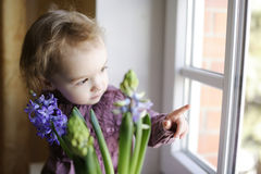 Adorable toddler girl sitting by the window Stock Photography