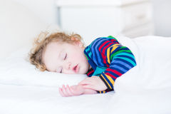 Adorable toddler girl taing a nap in a white bedroom. Adorable toddler girl taing a nap in a white sunny bedroom Royalty Free Stock Images