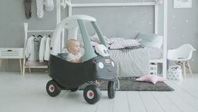 Cute infant playing in baby car in domestic imterior stock footage