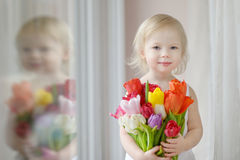 Adorable toddler girl with tulips by the window Royalty Free Stock Photos