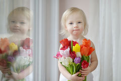 Adorable toddler girl with tulips by the window Royalty Free Stock Image