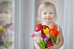 Adorable toddler girl with tulips by the window Stock Photo