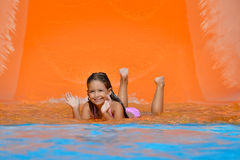 Adorable toddler girl on water slide at aquapark. Real toddler girl enjoying her summer vacation on water slide at aquapark Stock Photos