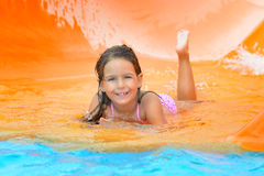 Adorable toddler girl on water slide at aquapark. Real toddler girl enjoying her summer vacation on water slide at aquapark Stock Photography