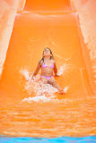 Adorable toddler girl on water slide at aquapark. Real toddler girl enjoying her summer vacation on water slide at aquapark Stock Photo