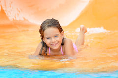 Adorable toddler girl on water slide at aquapark Royalty Free Stock Images