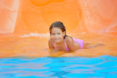 Adorable toddler girl on water slide at aquapark. Summer vacation Stock Photos