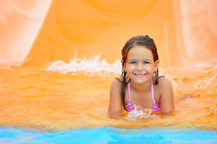 Adorable toddler girl on water slide at aquapark. Summer vacation Royalty Free Stock Photo