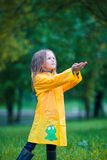 Adorable toddler girl wearing waterproof coat playing outdoors by rainy and sunny day Stock Images