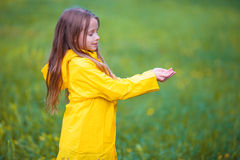 Adorable toddler girl wearing waterproof coat playing outdoors by rainy and sunny day. Adorable little girl happy standing under the rain outdoors Stock Photos