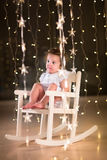 Adorable toddler girl in a white rocking chair in dark room with Christmas lights royalty free stock images