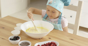 Adorable toddler at mixing bowl Stock Images