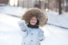 Adorable toddler playing snowballs outside Royalty Free Stock Image