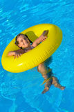 Adorable toddler relaxing in swimming pool Stock Photos