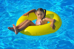 Adorable toddler relaxing in swimming pool Stock Image