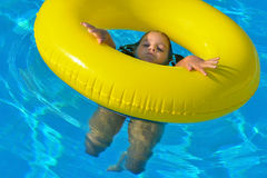 Adorable toddler relaxing in swimming pool Stock Images