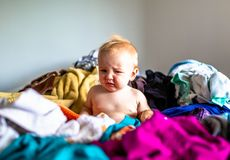 Toddler Sitting in Pile of Laundry on Bed royalty free stock image