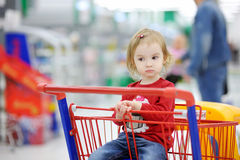 Adorable toddler sitting in shopping cart Royalty Free Stock Image
