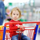 Adorable toddler sitting in shopping cart Stock Images