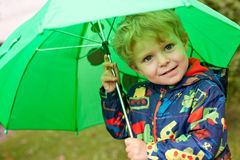 Adorable toddler under green rain umbrella autumn Stock Images