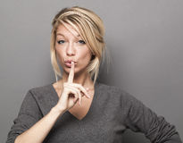 Adorable trendy woman asking to keep quiet for discretion Royalty Free Stock Images