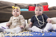Adorable twin babies playing with food stock images