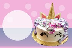 Adorable Unicorn cake with ice cream cone horn cake on pink and purple poka dotted background with space for copy. Adorable Unicorn cake with ice cream cone horn royalty free stock photography