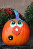 Adorable whimsical expression painted on Halloween pumpkin. Cute face of whimsical character painted on bright orange background of Halloween pumpkin, with hardy stock image