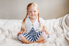 Adorable white Caucasian smiling preschool girl sitting on bed looking in camera. Portrait of cute adorable white Caucasian smiling preschool girl sitting on bed royalty free stock images