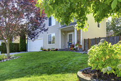 Adorable white house with nice front lawn and trees. Royalty Free Stock Images