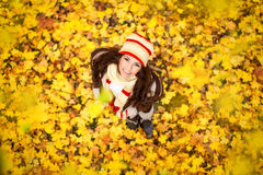 Adorable woman in the autumn park. Adorable young woman with autumn leaves in the park, top view royalty free stock photo
