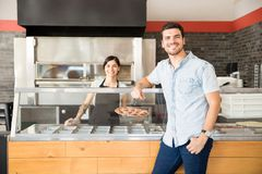 Adorable woman chef and handsome customer standing at pizza shop. Handsome men ordering for pizza with women chef holding pepperoni cheese pizza standing behind royalty free stock images