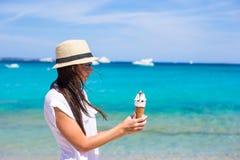 Adorable woman eating ice cream on tropical beach Stock Image