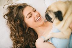 Adorable woman hugging her pug dog in bed. Happy family moments royalty free stock photos