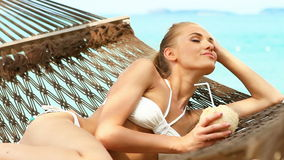Adorable woman laying and drinking from coconut. Adorable woman laying at hammock and drinking from coconut stock video