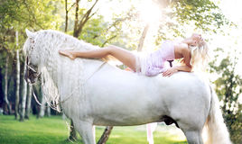 Adorable woman lying on the majestic horse royalty free stock image
