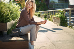 Adorable woman sitting on the public bench Royalty Free Stock Photos
