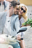 Adorable woman sitting on the scooter with her boyfriend Royalty Free Stock Photo