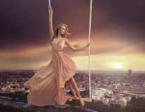 Adorable woman swinging above the city Royalty Free Stock Images