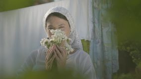 Adorable woman with white shawl on her head sniffing daisies looking at camera near the clothesline outdoors. Washday. Attractive senior woman with white shawl stock video