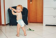 Adorable 1 year old baby boy helping with cleaning. Looking back over the shoulder, wearing diaper, holding a mop Royalty Free Stock Photo
