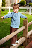 Brave Boy Child. An adorable 4 year old boy child with a chubby face, bravely daring to stand on a fence rail. Shallow depth of field royalty free stock image