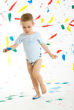 Adorable 3 year old boy child creatively stains on the wall. Adorable 3 year old boy child creatively stains on the wall, floor with colourful paint. Mess of Royalty Free Stock Image