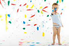 Adorable 3 year old boy child creatively stains on the wall. Adorable 3 year old boy child creatively stains on the wall, floor with colourful paint. Mess of Stock Image